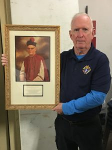 Faithful Navigator Cameron Meeker with a portrait of Msgr. James Fitzgerald.